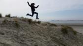 Mann springt in den Dünen